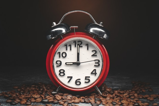 暗い壁に時計と茶色のコーヒー種子の正面図