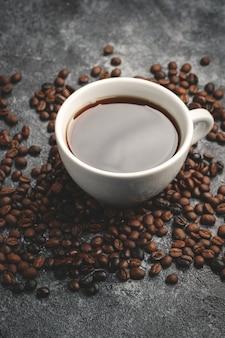 暗い壁にコーヒーのカップと茶色のコーヒーの種の正面図