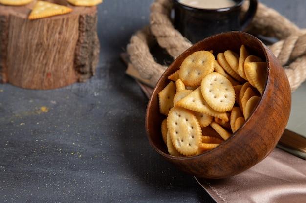 회색 표면에 우유와 함께 칩과 크래커 갈색 접시의 전면보기