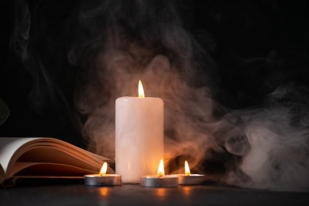 Вид спереди горящей свечи на темной поверхности