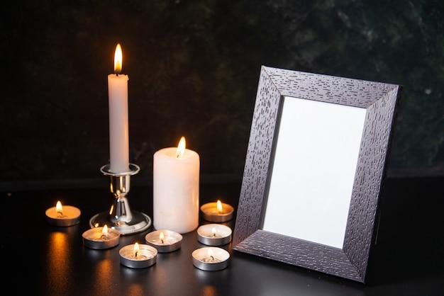 Вид спереди горящих свечей как память о упавших на черную поверхность