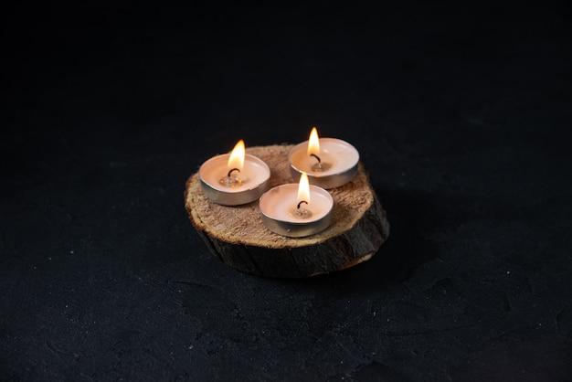 Вид спереди горящих свечей на темной поверхности
