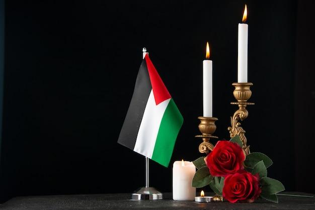 Вид спереди горящих свечей с палестинским флагом на темной поверхности