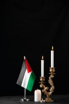 暗い表面にパレスチナの旗が付いている燃えているろうそくの正面図