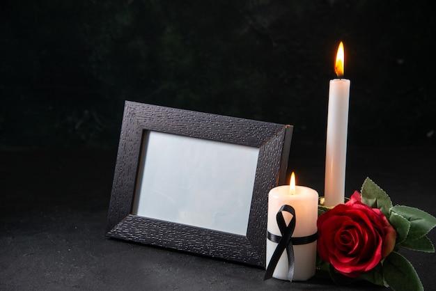 어두운 표면에 붉은 꽃과 촛불을 굽기의 전면보기