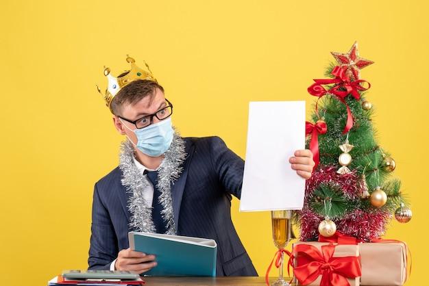 Вид спереди делового человека, проверяющего бумагу, сидя за столом возле рождественской елки и подарков на желтой стене