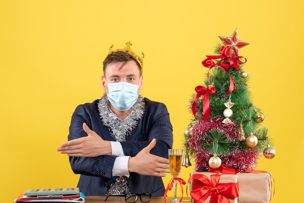 クリスマスツリーの近くのテーブルに座って手を交差し、黄色の壁に提示するビジネスマンの正面図
