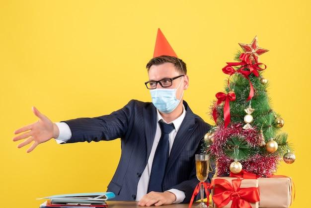 クリスマスツリーの近くのテーブルに座って手を差し伸べるビジネスマンと黄色の壁にプレゼント