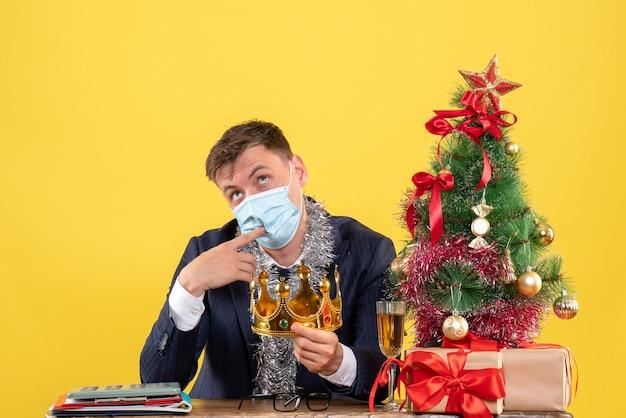 Вид спереди делового человека, держащего корону, сидящего за столом возле рождественской елки и подарков на желтом
