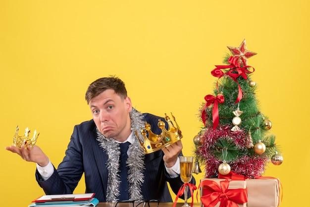 Вид спереди делового человека, держащего короны в обеих руках, сидя за столом возле рождественской елки и подарков на желтом