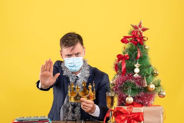 Вид спереди делового человека, держащего свою корону, сидящего за столом возле рождественской елки и подарков на желтом