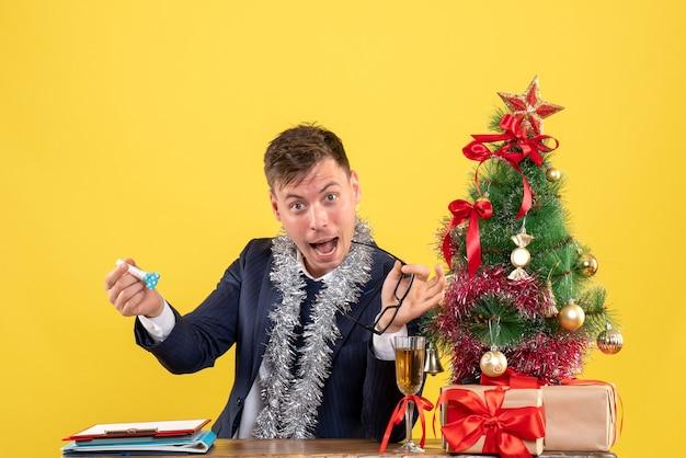 Вид спереди делового человека, держащего шумогенератор, сидящего за столом возле рождественской елки и подарков на желтом