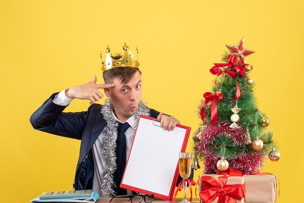 クリスマスツリーの近くのテーブルに座っている彼の寺院に指銃を保持し、黄色で提示するビジネスマンの正面図