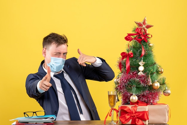 クリスマスツリーの近くのテーブルに座って、黄色で提示する電話サインを作るビジネスマンの正面図