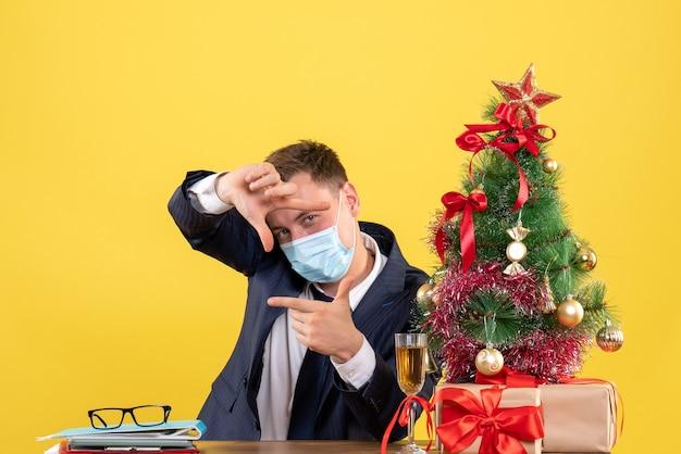 クリスマスツリーの近くのテーブルに座って、黄色で提示するカメラの看板を作るビジネスマンの正面図