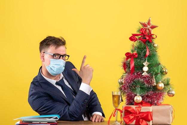 クリスマスツリーの近くのテーブルに座って、黄色のプレゼントに指銃を作るビジネスマンの正面図