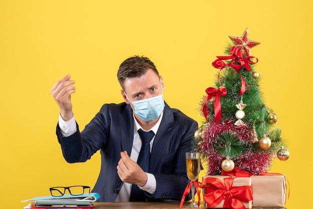 Вид спереди делового человека, делающего деньги, знак, сидящий за столом возле рождественской елки и подарки на желтом