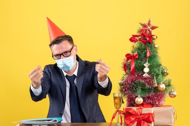 Вид спереди делового человека, делающего деньги, знак пальцами, сидящими за столом возле рождественской елки и подарками на желтом