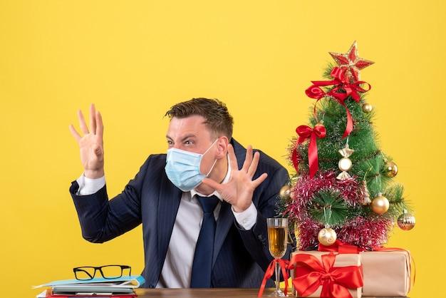 クリスマスツリーの近くのテーブルに座って怖いジェスチャーをして黄色で提示するビジネスマンの正面図