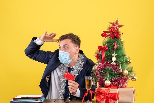 Вид спереди делового человека, наблюдающего за чем-то сидящим за столом возле рождественской елки и подарками на желтом