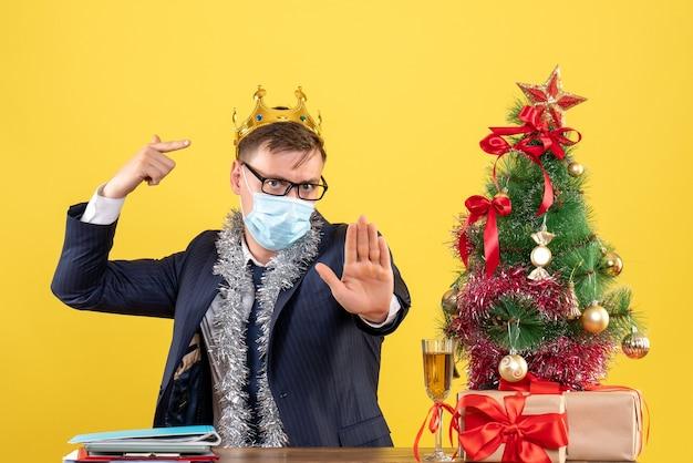 Вид спереди делового человека, указывающего на свою корону, сидящего за столом возле рождественской елки и подарков на желтом