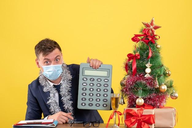 Вид спереди делового человека, показывающего калькулятор, сидящего за столом возле рождественской елки и подарков на желтом