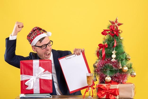 크리스마스 트리 근처 테이블에 앉아 승리 제스처를 보여주는 사업가의 전면보기와 노란색 선물.