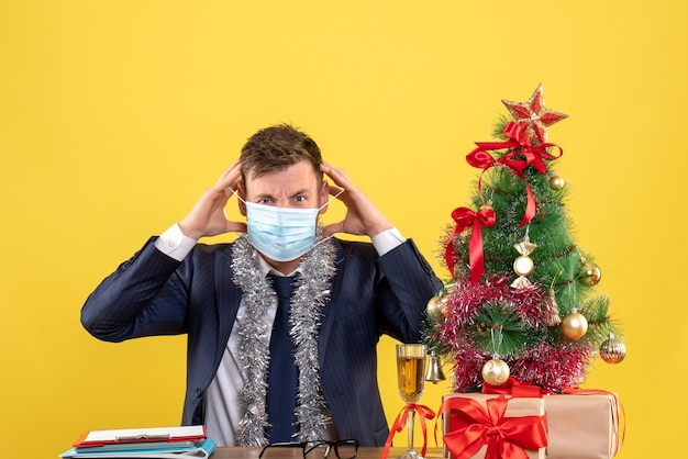 크리스마스 트리 근처 테이블에 앉아 그의 마스크를 벗고 비즈니스 남자의 전면보기와 노란색에 선물.