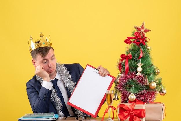 Вид спереди делового человека с короной, проверяющего бумагу, сидящего за столом возле рождественской елки и подарков на желтом