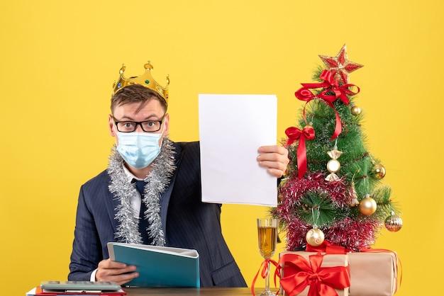 Вид спереди делового человека с короной, проверяющего документы, сидящего за столом возле рождественской елки и подарков на желтом