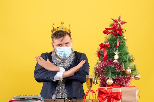 Вид спереди делового человека с короной, скрещивающей руки, сидящего за столом возле рождественской елки и подарков на желтом