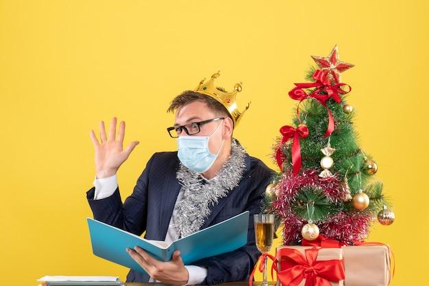 Вид спереди делового человека с короной, приветствующего кого-то, сидящего за столом возле рождественской елки и подарков на желтом