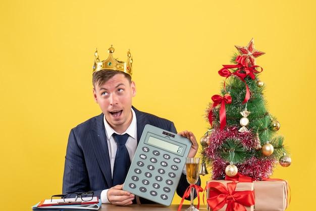 Вид спереди делового человека с короной, держащего калькулятор, сидящего за столом возле рождественской елки и подарков на желтом