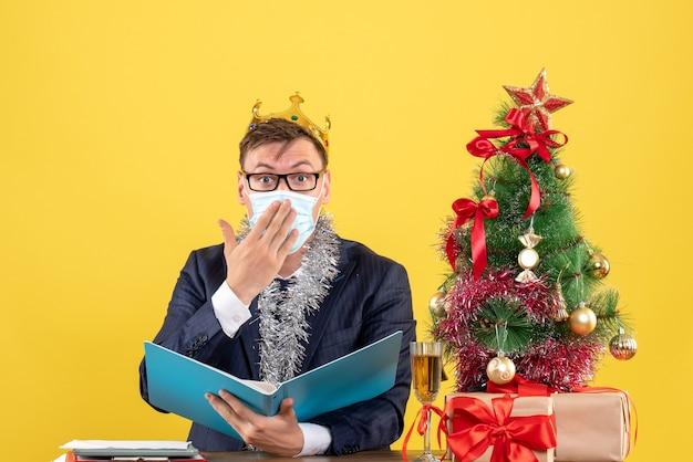 Вид спереди делового человека с короной, держащего файл документа, сидящего за столом возле рождественской елки и подарков на желтом