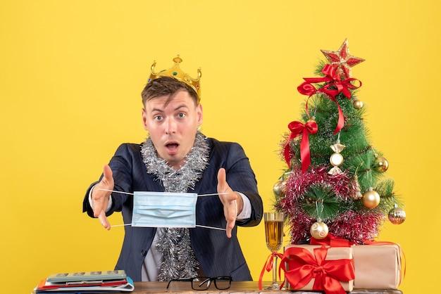 Вид спереди делового человека с короной, держащего маску, сидящего за столом возле рождественской елки и подарков на желтом