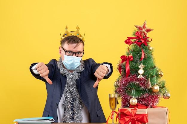 Вид спереди делового человека с короной, делающего большой палец вниз знак, сидящего за столом возле рождественской елки и подарков на желтом