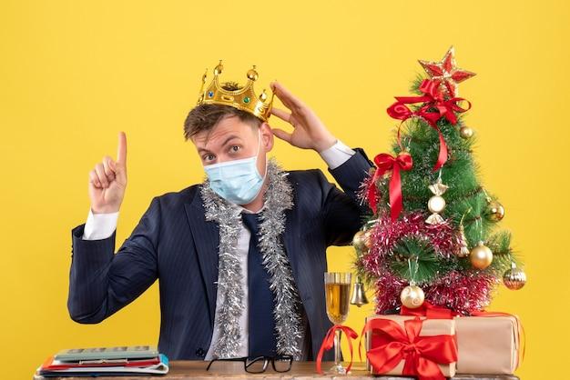 Вид спереди делового человека с короной, указывающей на высокий, сидя за столом возле рождественской елки и подарков на желтом