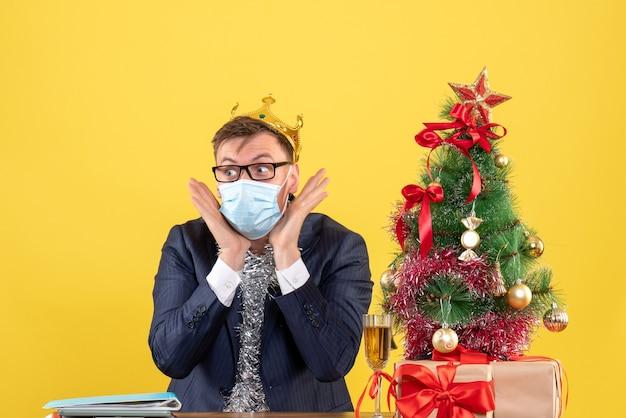 Вид спереди делового человека с короной, сидящего за столом возле рождественской елки и подарков на желтом