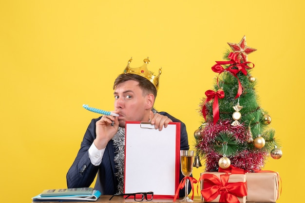 Вид спереди делового человека с короной, использующего шумовщик, сидящего за столом возле рождественской елки и подарков на желтом