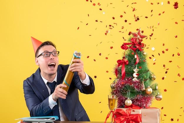 クリスマスツリーの近くのテーブルの後ろに立って黄色でプレゼントパーティーポッパーを使用してパーツキャップを持つビジネスマンの正面図