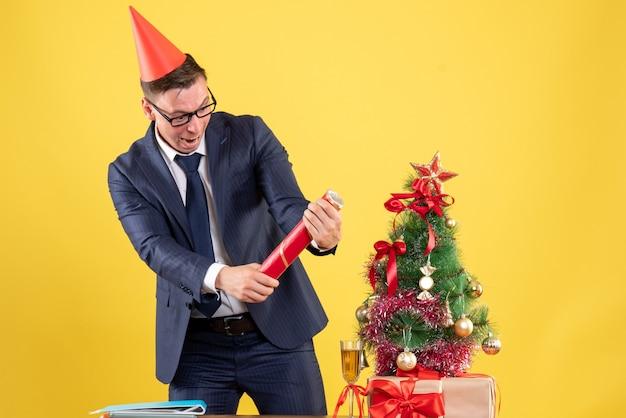 クリスマスツリーの近くに立っているパーティーキャップと黄色のプレゼントとビジネスマンの正面図