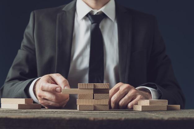 Вид спереди бизнесмена на своем столе, делая стопку деревянных колышков
