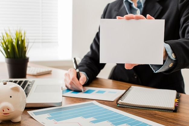 Вид спереди бизнесмена в офисе, холдинг чистый лист бумаги