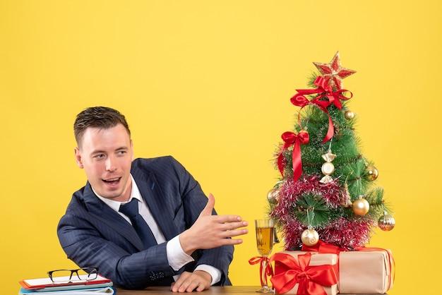 노란색에 크리스마스 트리와 선물 근처 테이블에 앉아 손을주는 사업가의 전면보기