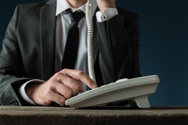 Вид спереди бизнесмена в элегантном костюме, набирающего телефонный номер с помощью белого стационарного телефона.