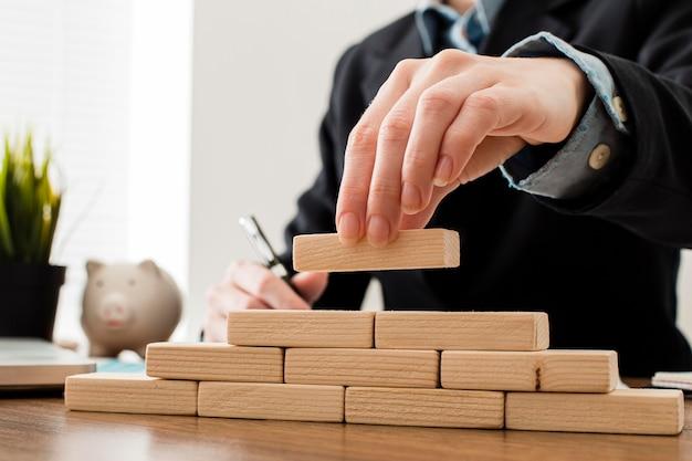 木製のビルディングブロックを持つビジネスマンの正面図