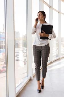 Вид спереди деловой женщины, держащей переплет и говорящей по телефону
