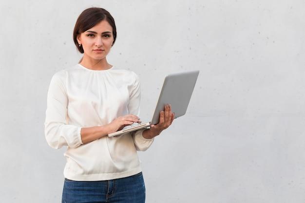 Вид спереди бизнесвумен, держащего ноутбук на открытом воздухе