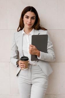 Вид спереди бизнес-леди, держащей планшет и чашку кофе