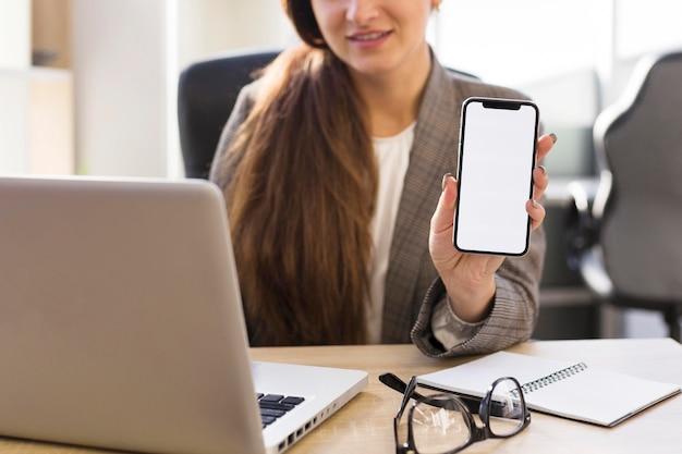 Вид спереди бизнес-леди в офисе, держащем смартфон